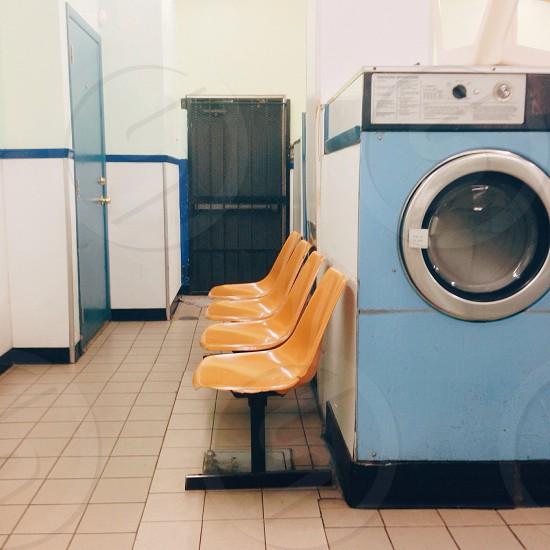 blue and grey front load washing machine near orange chair photo