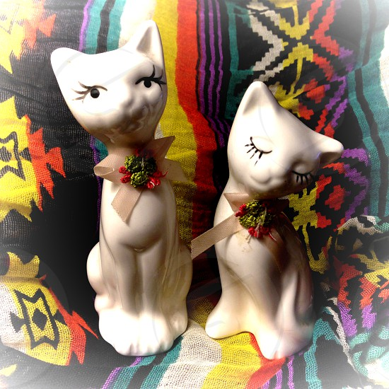 A pair of small retro cat figurines sit on a tribal background. photo