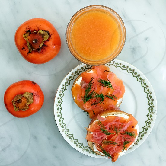 Breakfast table bagel with lox and juice.  photo
