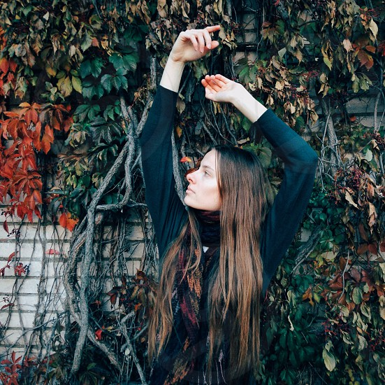 woman with brown long hair in black long sleeved shirt standing near veins during daytime photo