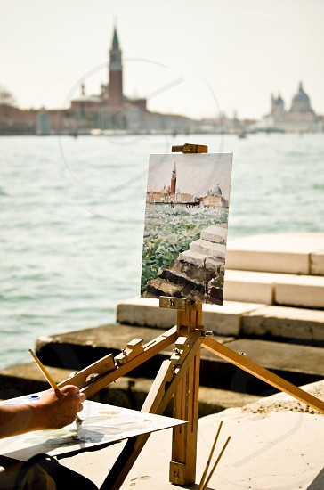 person painting the water and buildings photo