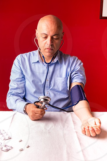 Hypertensive patient performing a blood pressure auto test / man self-monitoring of blood pressure with a tensiometer photo
