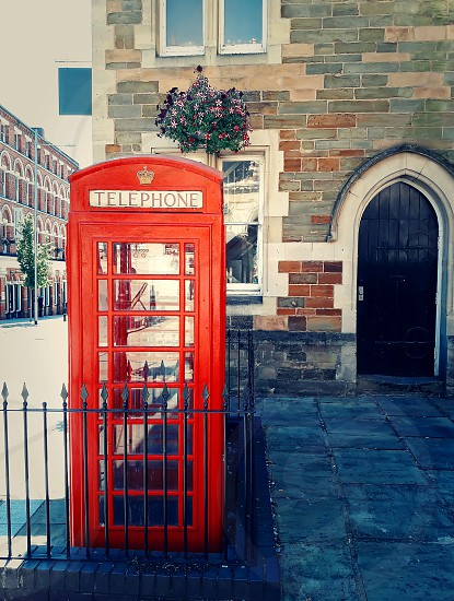 Traditional british red phone booth on the street near Guidhall Northampton England. photo