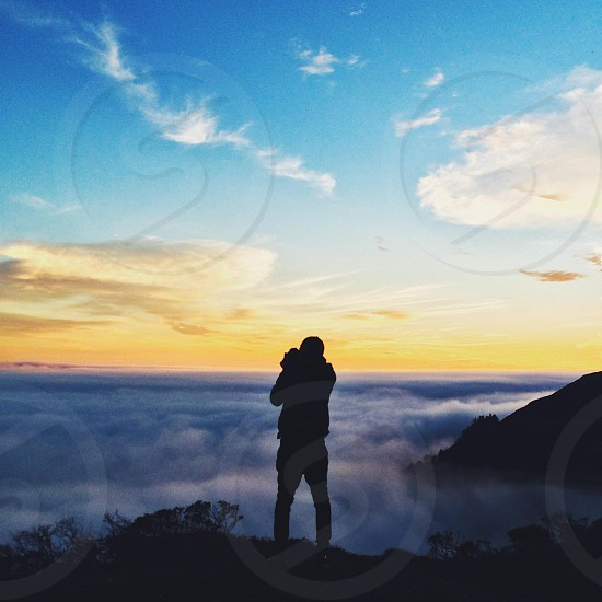 man silhoutte standing on hill cliff taking a photo photo