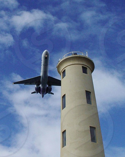 Airplane flying past lighthouse photo