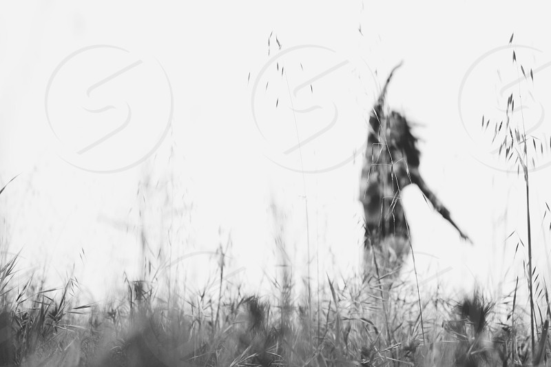 woman standing in fields grayscale photography photo