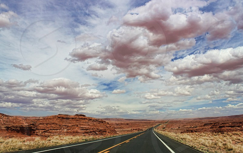 Long road through red rock country under low hanging white clouds. photo