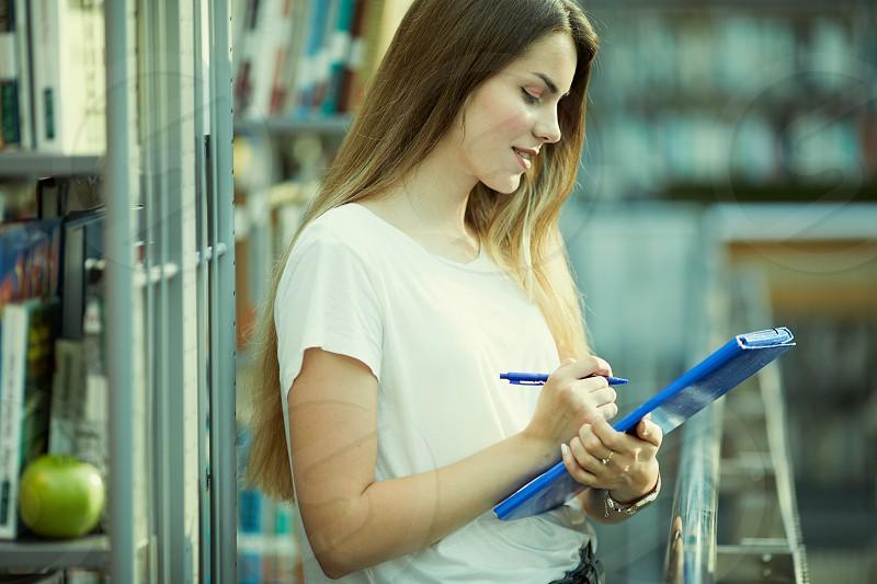 Pretty girl read blue book and smile to camera photo