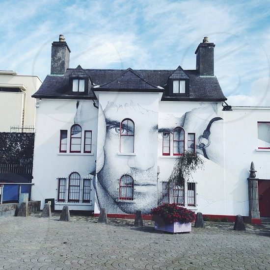 white concrete building with man's face painting photo