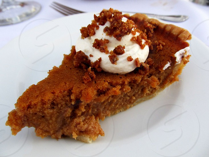 Sweet potato pie with whipped cream on white plate photo