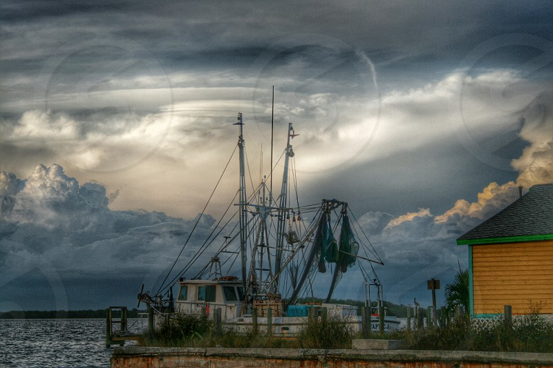 Fishing boat town building dock clouds sky stormy island horizon nature coastal landscape water photo