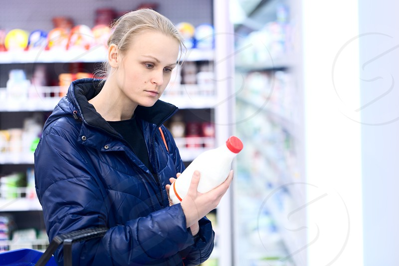 Woman in grocery holding a bottle of milk reading the label intently photo