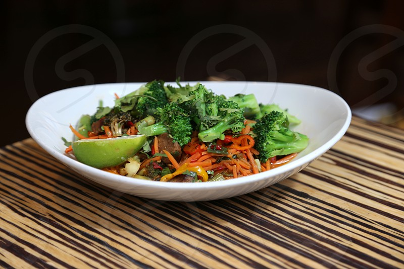 sliced carrots and broccoli mixed on white ceramic bowl photo