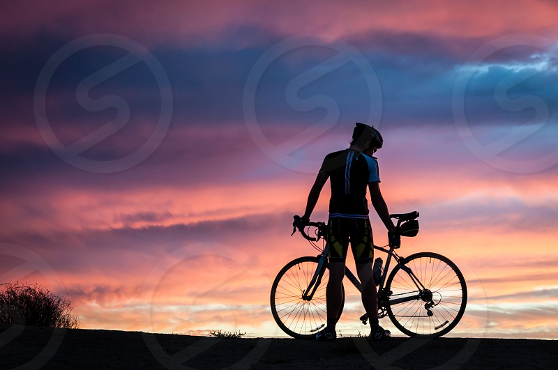Man with bicycle at sunset photo