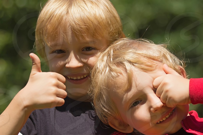 "Two blond boys (brothers). One of them hides his eyes with his hand the other shows a gesture ""OK"". photo"