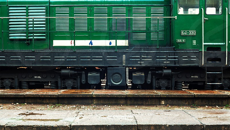 Details of big and green locomotive parked in station during bad weather cold rainy day.  photo