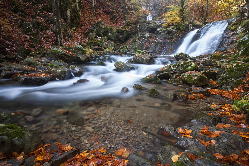 Nice effect of waterfall against the bright red hues of autumn photo