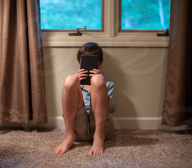 Boy tween playing on technology device in bedroom photo