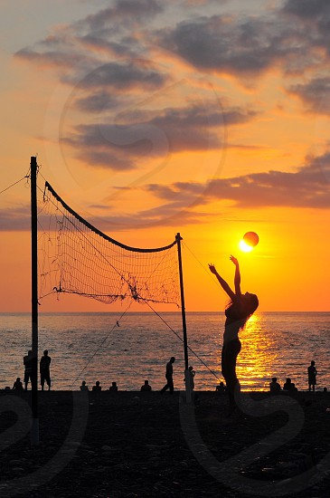 woman playing volley with sunset view on beach photo