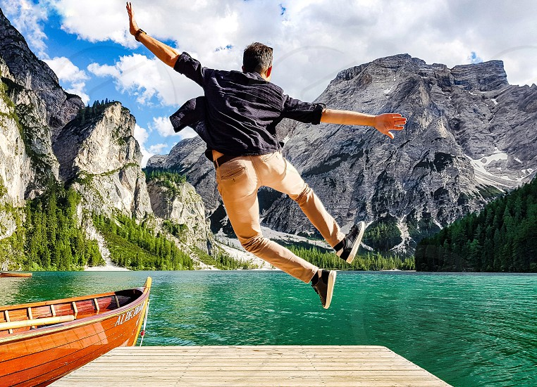 Man jumping with a lake and mountains in the background. photo