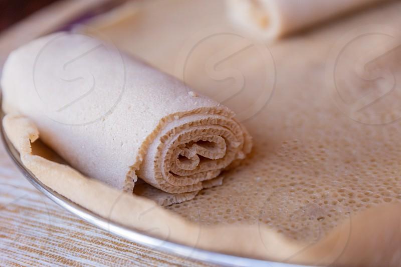 Injera is a sourdough flatbread made from teff flour.  It is the national dish of Ethiopia Eritrea Somalia and Djibouti photo