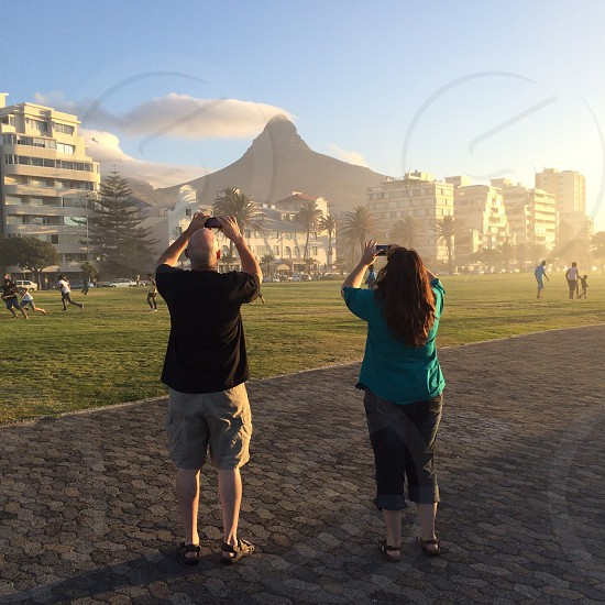 man and woman taking photo of volcano spewing white smoke behind hotels and football pitch photo