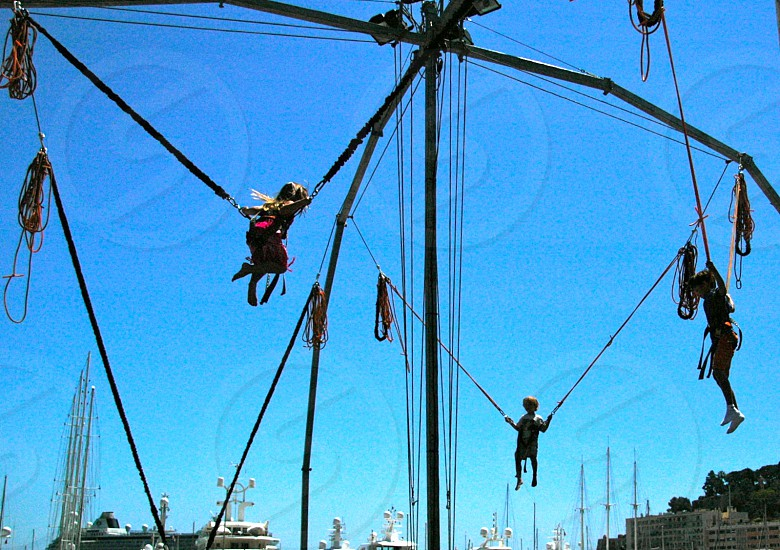 three children hanging from  suspended system beneath blue sky by marina photo