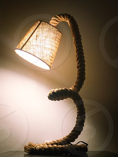 brown rope base figure brown shade table lamp turned on photo
