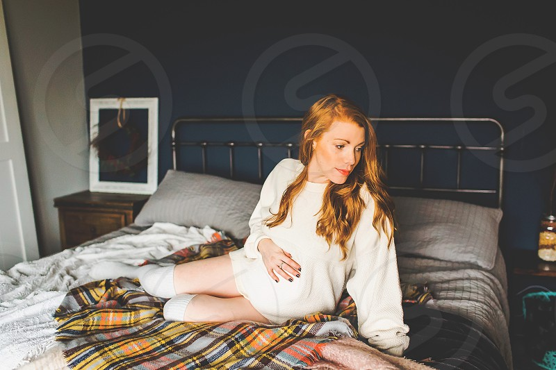 pregnant mom in bed at home during the winter months photo
