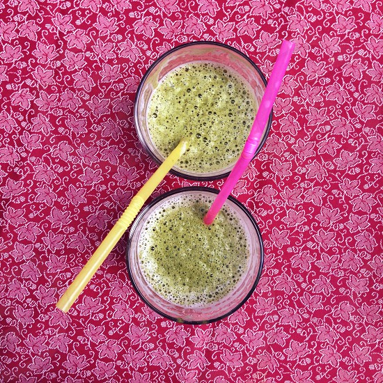 green beverage in 2 glass cup with yellow and pink straws photo