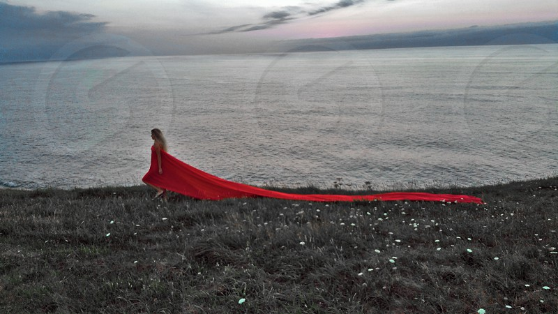 lady in red on the gray grass on the edge cliff photo