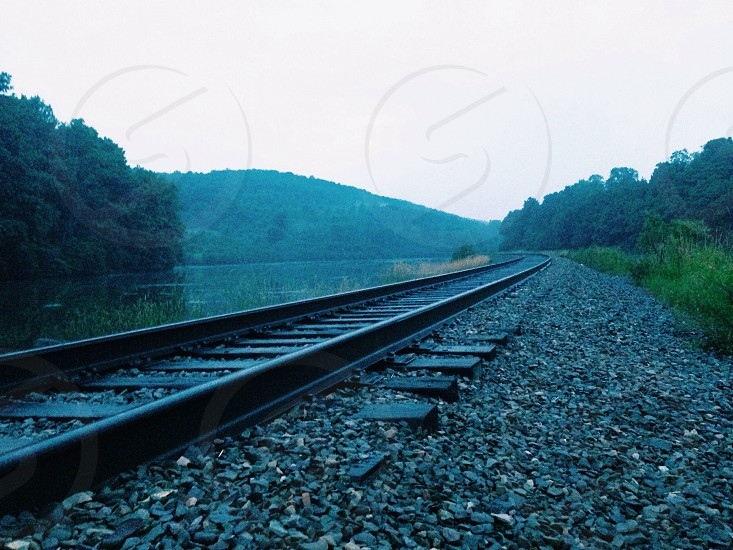 Green mountains set behind railroad track & ponds.  photo
