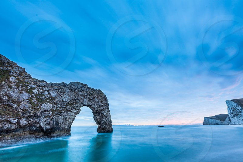 Sunset at Durdle Door on the Jurassic coast of Doset England in the uk featuring a natural geologically formed arch over the sea photo