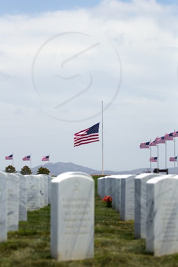 flags of united states of america waving under columns of gravestones under white sky during daytime photo