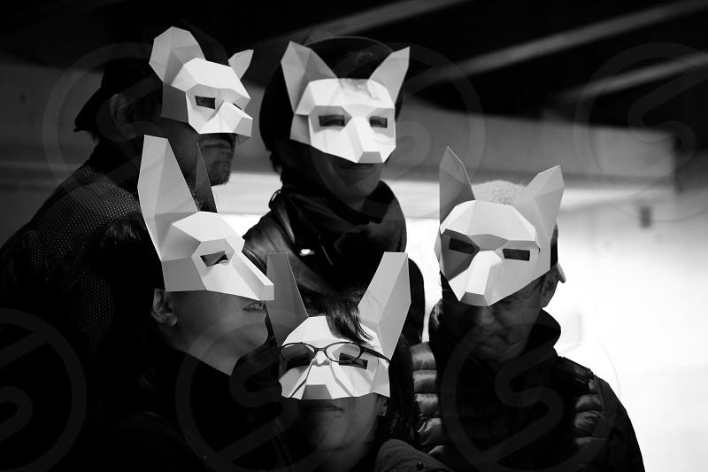 5 people wearing a white fox masks grayscale shot photo