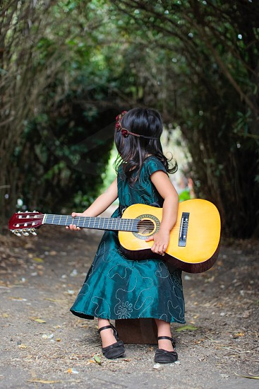 close-up photography of toddler girl wearing green cap-sleeved dress sitting on brown wooden stool holding brown classical guitar photo
