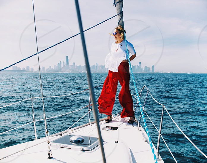 woman in white shirt and red pants standing on a sailboat photo