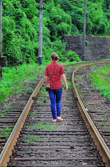 woman walking along train tracks photo