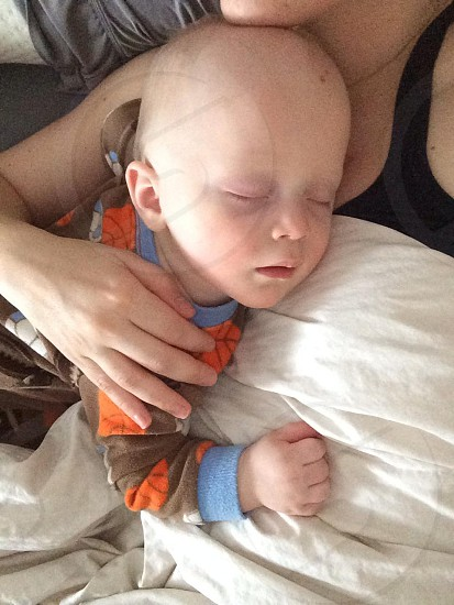 boy sleeping on his mothers chest photo