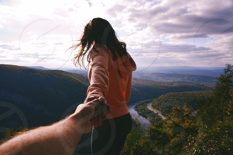 follow me photography of man and woman on mountain hill seeing divided mountain with river under white clouds blue skies daytime photo