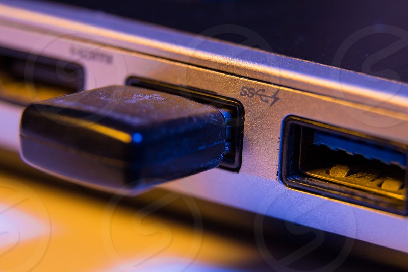 Closeup of USB flash drive inserted into port on the side of a laptop. photo
