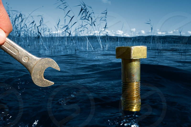Male hand holding a wrench in front of a large bolt coming out of the lake water on a sunny Autumn afternoon in Finland with ecology environmental protection and green concept idea. photo