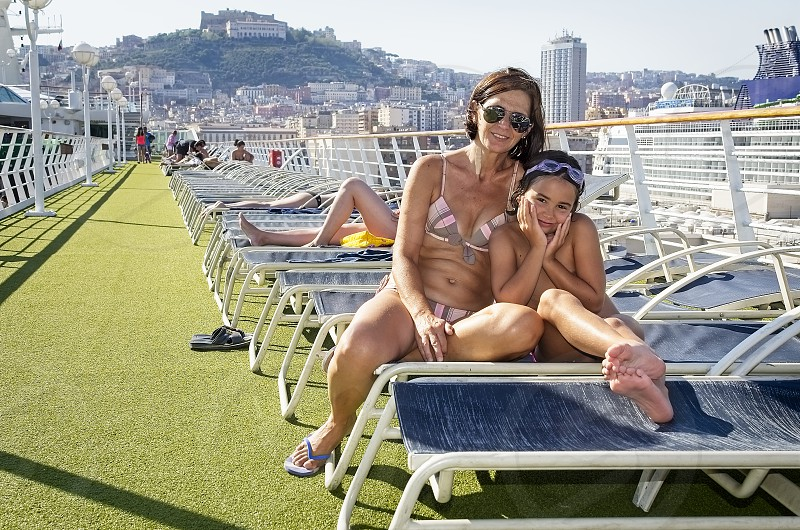 Mother and daughter sitting on the deck chairs of a cruise ship arriving at the port of Naples Italy photo