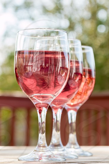 3 clear short stem wine glass with red wine in close up photography photo