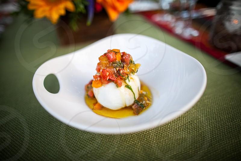 A beautiful appetizer of mozzarella on an outdoor farm table. photo