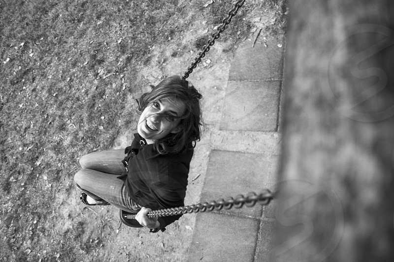 black and white photo of woman swinging on swings photo