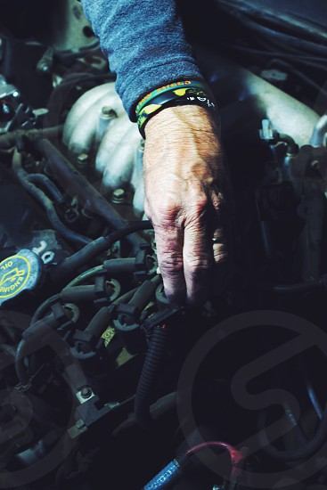 man wearing blue shirt checking the car engine photo