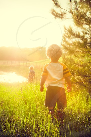 Kids Children Golden Hour Summer Evening Sunset Grass Boots Rain Boots Fence Water Pond Sky Backlit Trees Boys Brothers photo