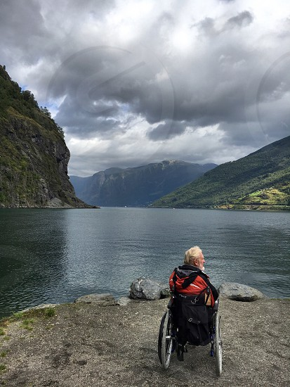 Man in wheelchair looking at fjord in Flamm Norway photo