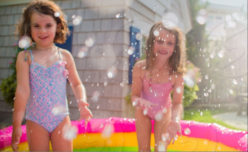 2 girls in inflatable pool in garden photo
